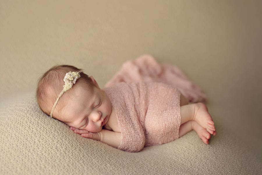 Newborn Photo of baby girl wearing a flower tie back from Ivy and Nell Baby wrapped in pink.