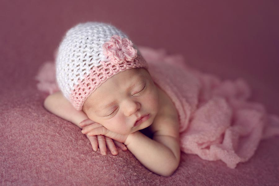 Newborn girl photography photos wearing pink hat with flower made by mom.