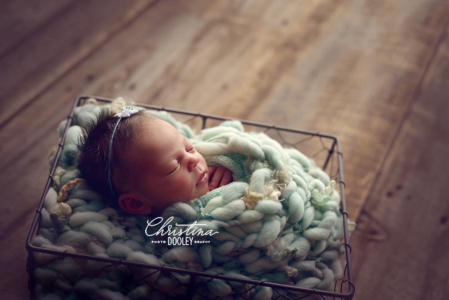 Side angle photo of newborn girl bundled in a large knit blanket in a wire basket