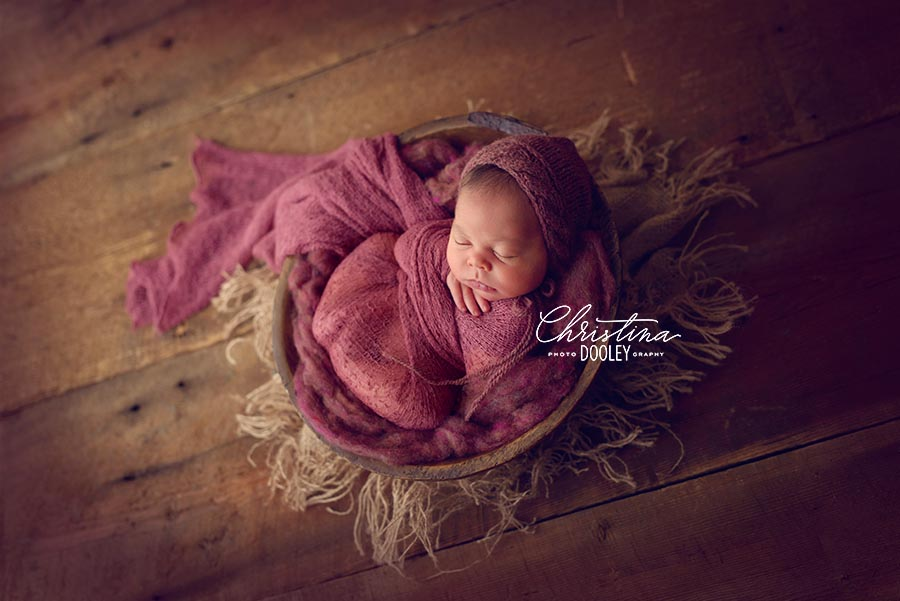 Pull back image of newborn girl swaddled and posed in a vintage bowl