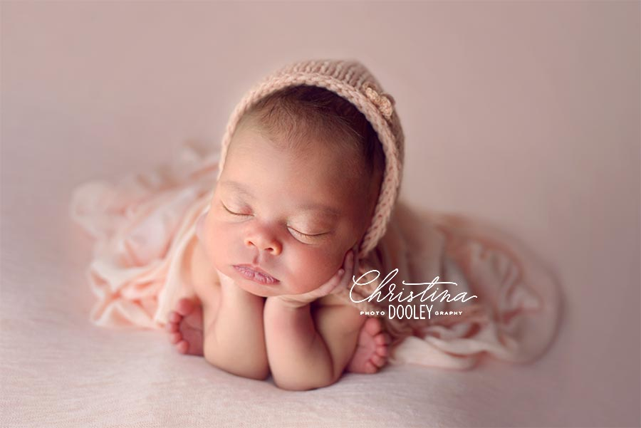 Baby girl in posed on peach in the newborn froggy pose
