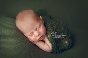 Baby boy in womb pose on green with a green knit blanket wrapped around him