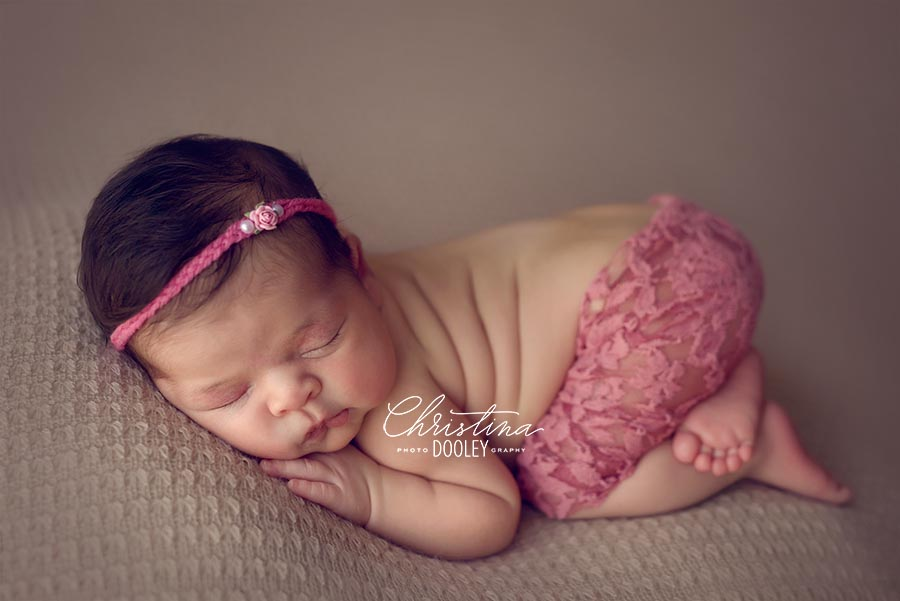 Baby girl photography session posed in tushie up pose on neutral color wearing pink lace pants.