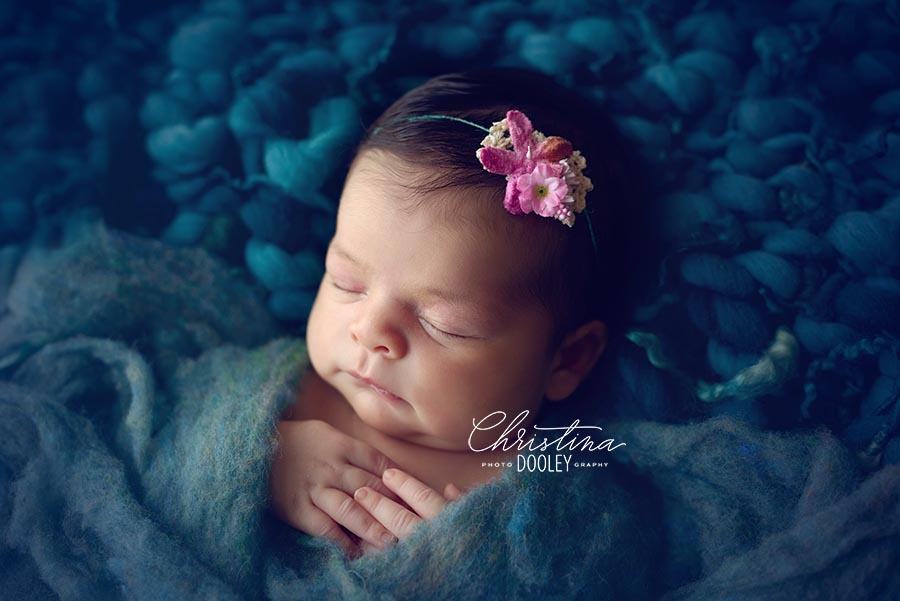 Newborn sleeping on teal bump blanket and wrapped in teal fluff wearing a pink tie back.