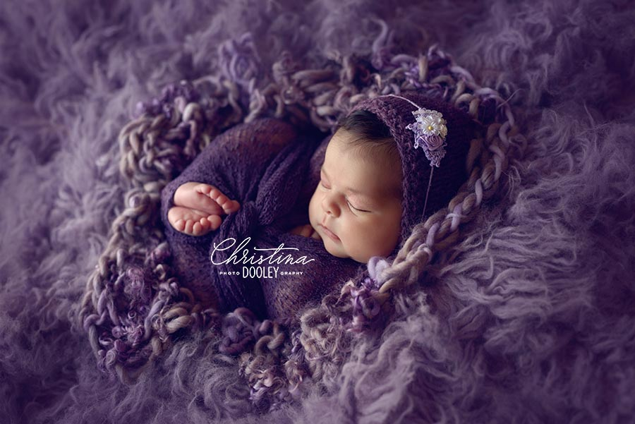 Baby girl wrapped in purple laying on a purple flokati rug wearing a bonnet from Wild Blossom Props