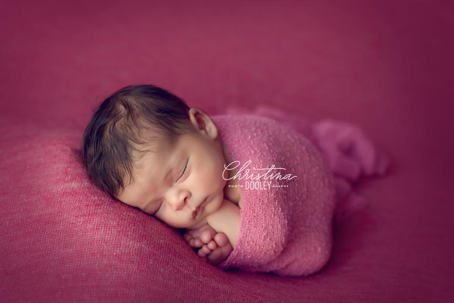 Newborn Photo session baby posed in taco pose wrapped in pink