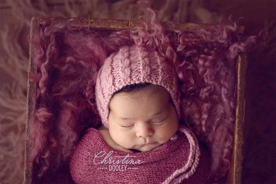Baby in a box stuffed with pink curly fur wearing a pink bonnet