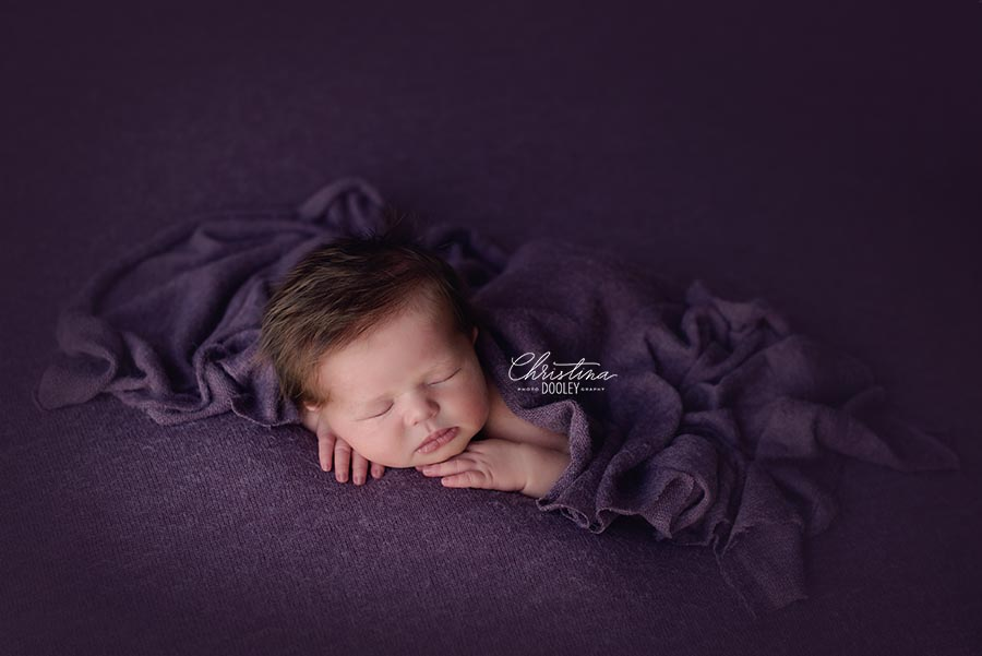 Newborn baby girl with a ton of hair posed with beautifully and covered in a purple wrap from AR Backdrops