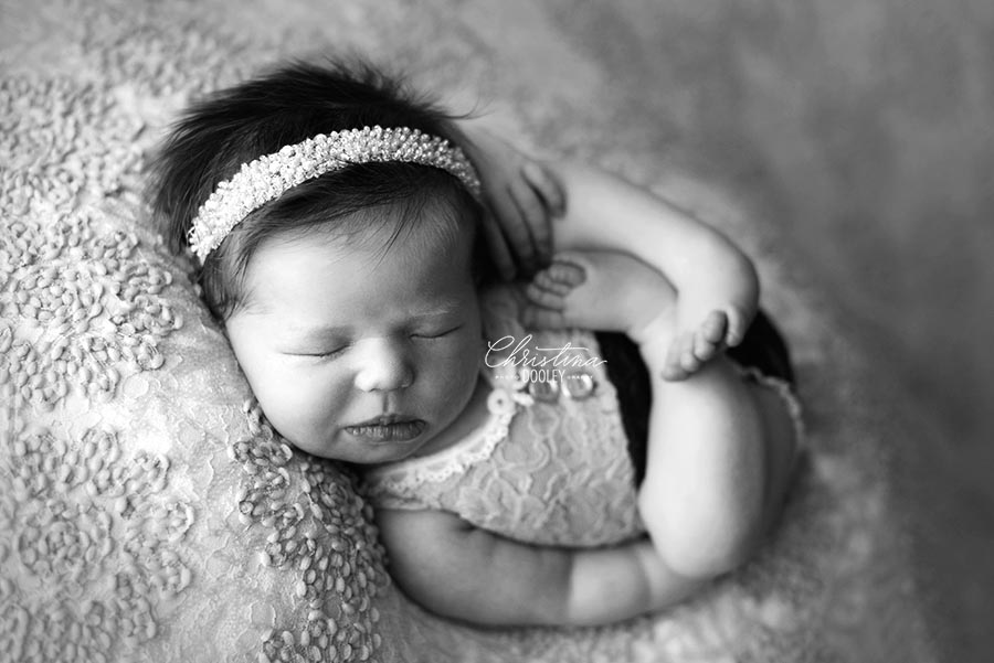Black and White image of newborn wearing a romper on a very girl background in the huck finn or womb pose for her baby photo session in Denver, Colorado.