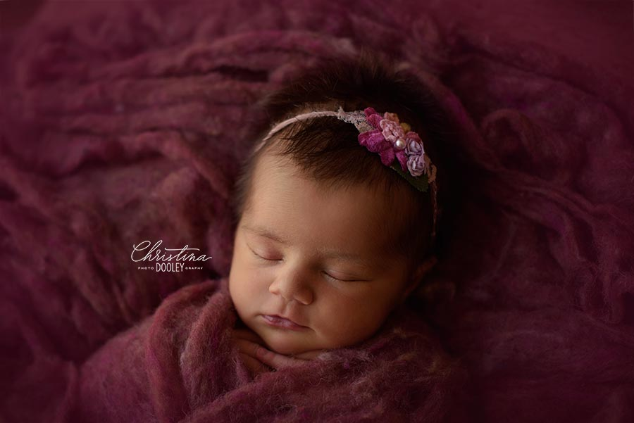 Newborn Girl all tucked in raspberry colored fluff from Oh so Fleeting wearing a pink headband from Princess and the Pea prop shop photographed in Denver, Colorado