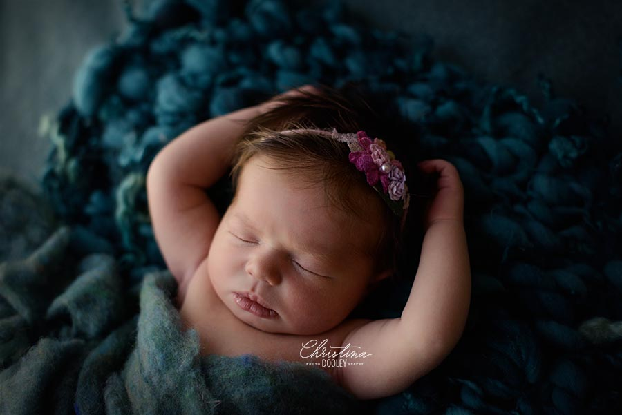 Baby girl sleeping on a chunky teal knit blanket from Mama Knits and wearing a tie back from Princess and the Pea Prop shop