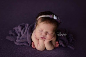 Baby girl posed in froggy pose on a purple background wrapped in a purple wrap all from AR Backdrops.
