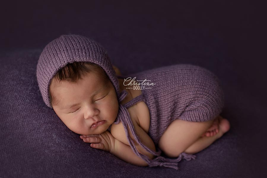 Baby Girl in a purple romper and bonnet from Zoe and Oliver posed on purple in Colorado