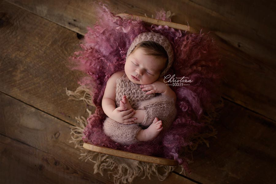 Newborn posed for her baby photos in a baby bed from Photoblocks and pink fur from Felt Fur wearing a romper from Lemon and Pearl Design.
