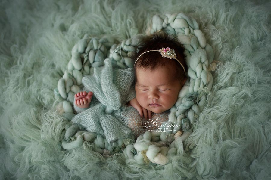 Baby girl posed for her newborn photography session in Denver on mint fur.