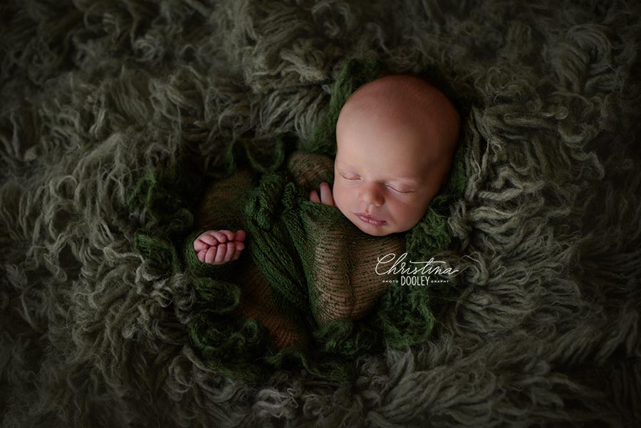 Newborn boy posed on a green flokati from JD Vintage props and swaddled in a knit green blanket from Wild Blossom Props for his baby photos.