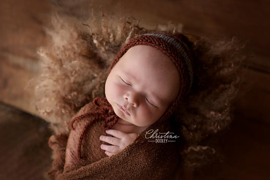 Newborn Baby boy swaddled in brown with a brown knit hat from Wild Blossom Props posed in a wooden bed with curly fur from Felt Fur