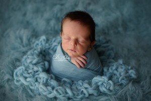 Baby portrait in the potato sack pose on teal