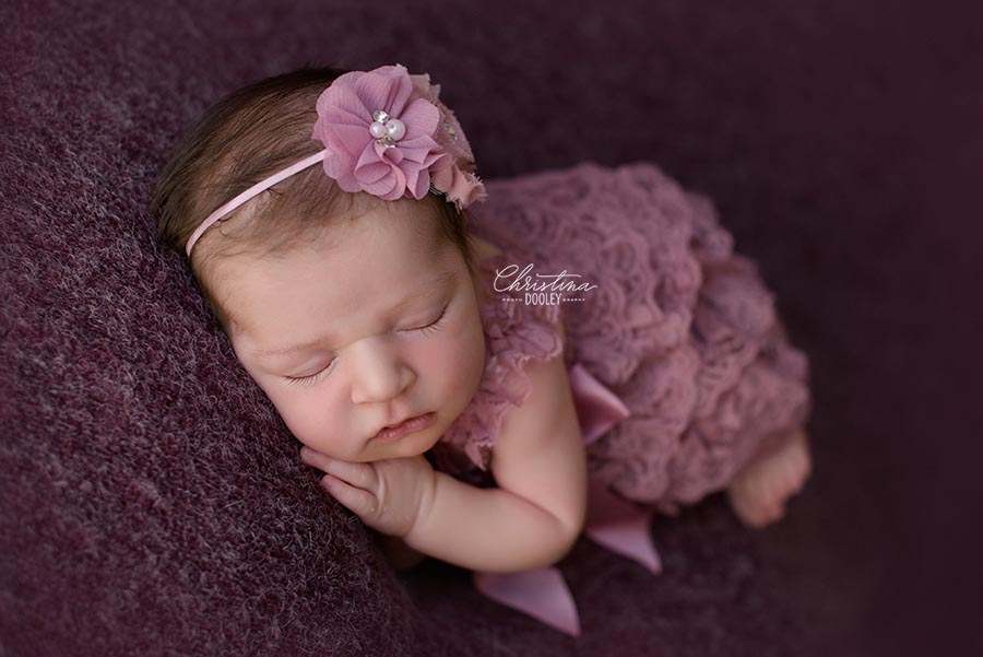 Baby girl wearing a dusty purple lace romper in side lying pose