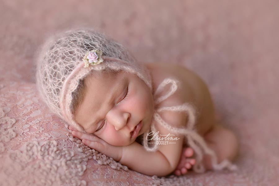 Baby girl posed in taco pose wearing a pink open knit bonnet with a pink flower tieback