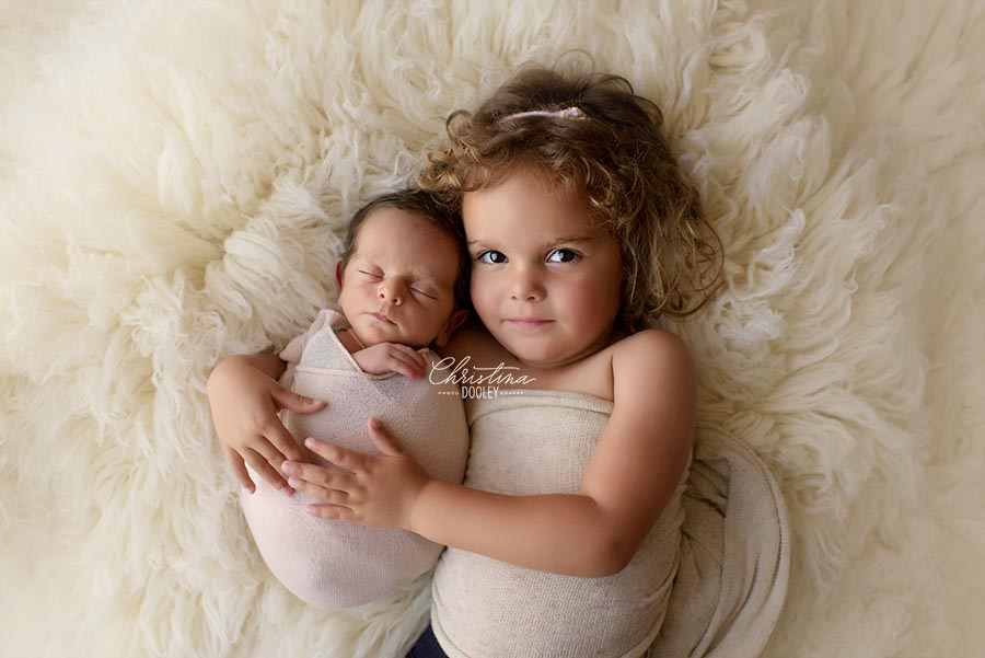 Baby boy and Sister photographed on cream fur from Luneberry in Denver Colorado studio