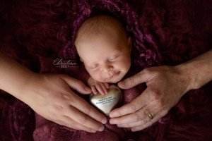 Rainbow baby girl cupping the silver heart her sister now rest in with mom and dad holding baby girl and heart as well.