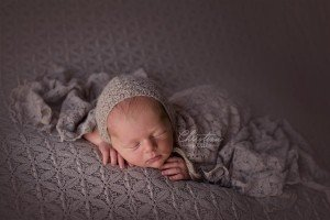 Baby photographed on a silvery beige flower background wearing a bonnet from Sweetie Pea Boutique.