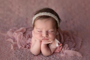 Newborn baby girl photographed on a girly pink backdrop in froggy pose