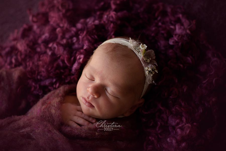 Newborn Photography Denver - Baby Posed on a rose colored blanket from Mama knits and wrapped in fluff from Oh so fleeting
