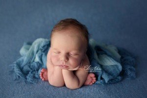 Newborn baby photography, baby photographed on blue in froggy pose