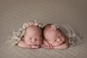 Twin newborns photographed together wearing headbands from Ivy and Nell