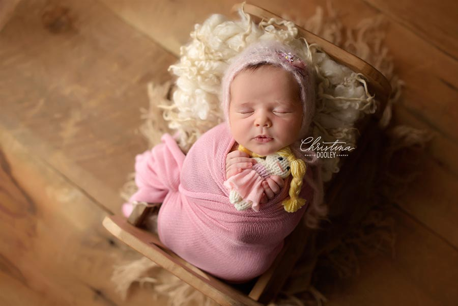 Newborn Portait, baby posed in a wooden bed swaddled in pink holding her first doll from Sweetie Pea Boutique