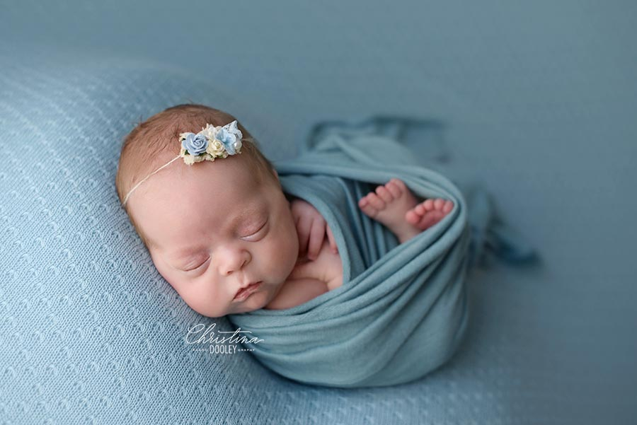 Newborn girl photographed in baby blue