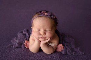 Newborn baby portraits photographed in Denver on purple wearing a tie back from Ivy and Nell Baby