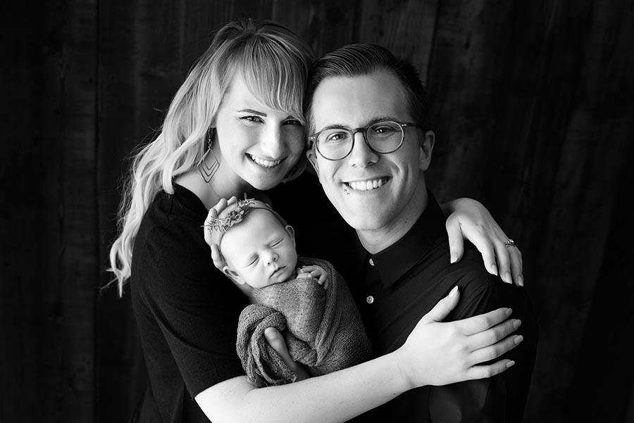 Happy new parents posing for their newborn family photos in Denver Colorado