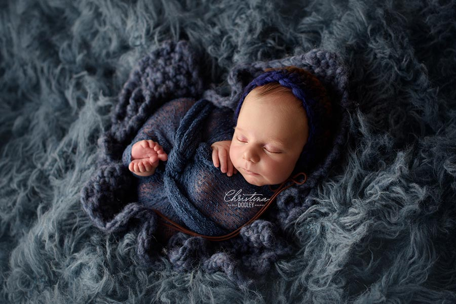 Baby boy swaddled in blue and nestled in a blue flokati from JD Vintage Props