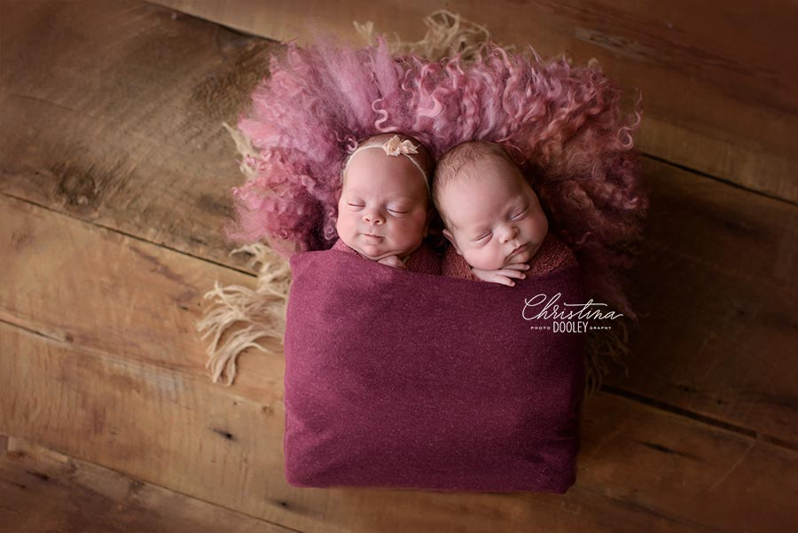 Twin babies wrapped in a raspberry swaddled and photographed together in a box.