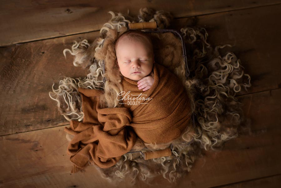 Baby wrapped in copper color swaddle in a basket