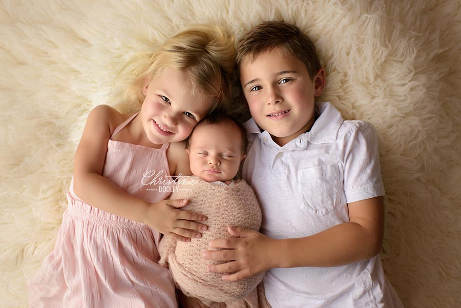 Sibling portrait with their new baby sister posed on a flokati from Luneberry