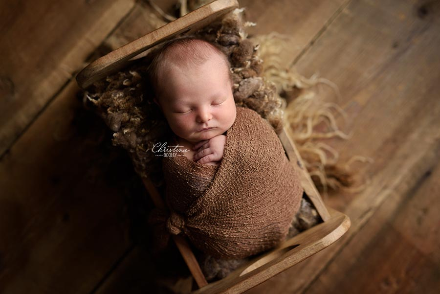 Newborn boy wrapped in a stretchy brown wrap in a wood bed make by Original Photoblocks