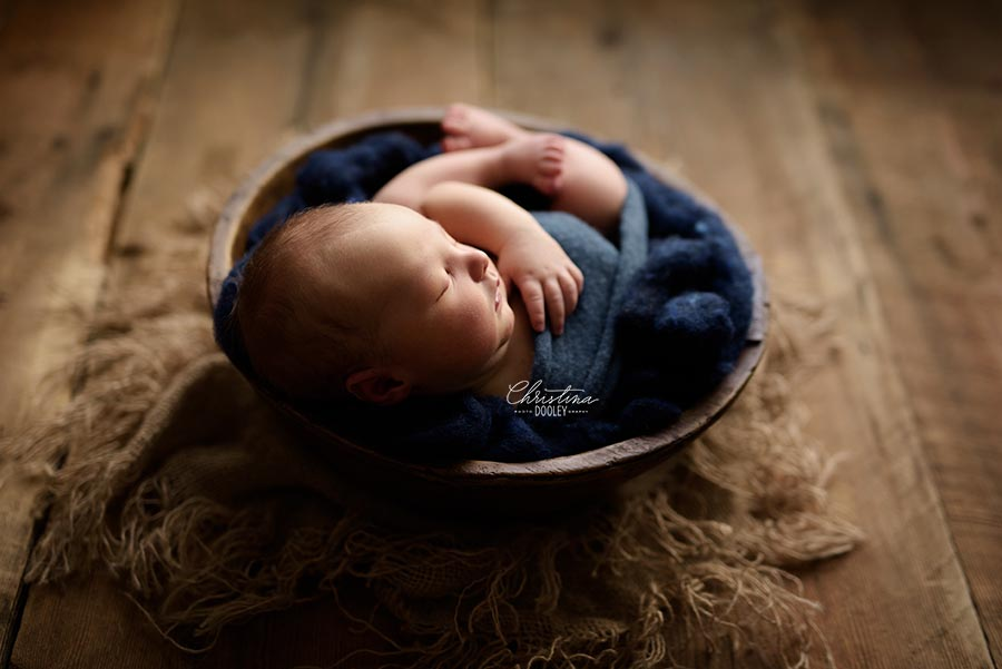 Dramatically lit image of baby boy in a bowl photographed from the side.