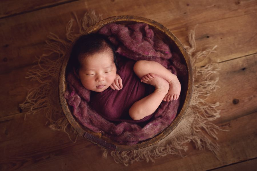 Colorado Baby posed and photographed in a wine colored wrapped in a bowl