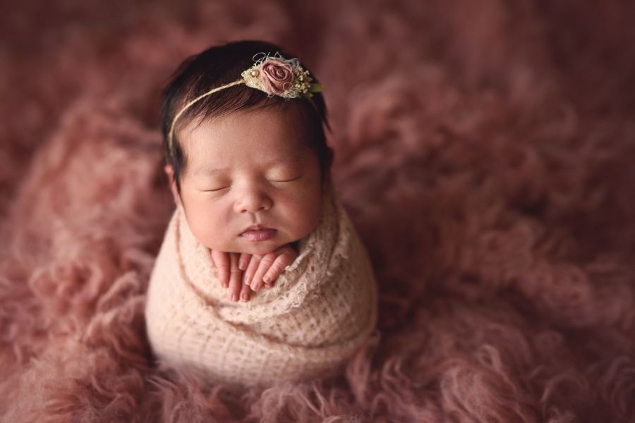 Baby Girl swaddled in pink in potato pose wearing a tie back from Ivy and Nell Baby.