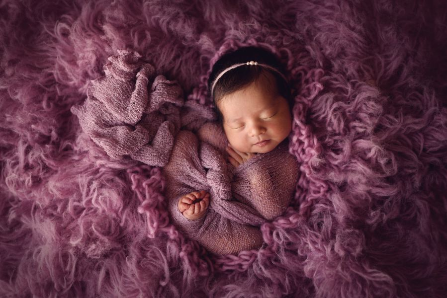 Denver Newborn Posed with her little feet sticking out on a purple fur