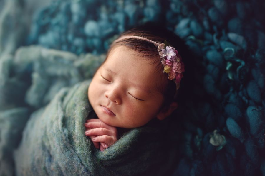 Newborn photographed wrapped in teal fluff wearing a tie back from Princess and the Pea