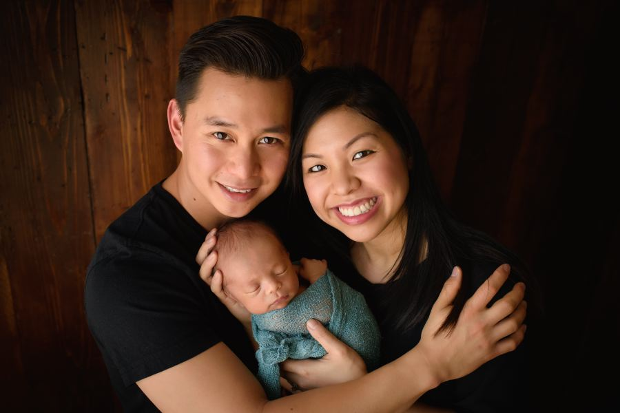 First family portrait of new family of three with their newborn baby