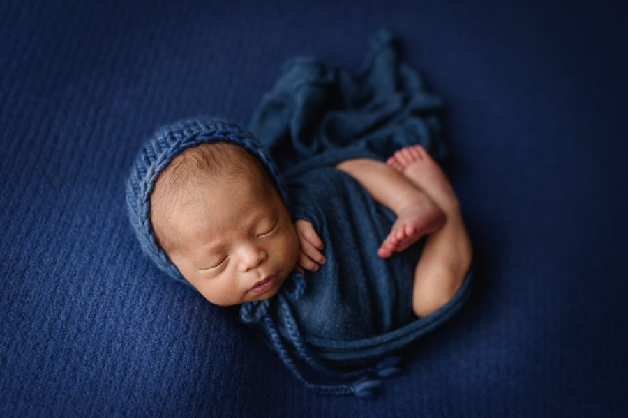 Newborn baby photographed in blue in womb pose