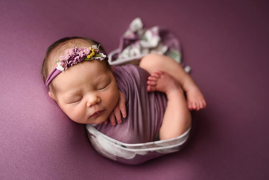 Newborn Photo of baby girl wrapped in a floral wrap posed in womb pose in Denver