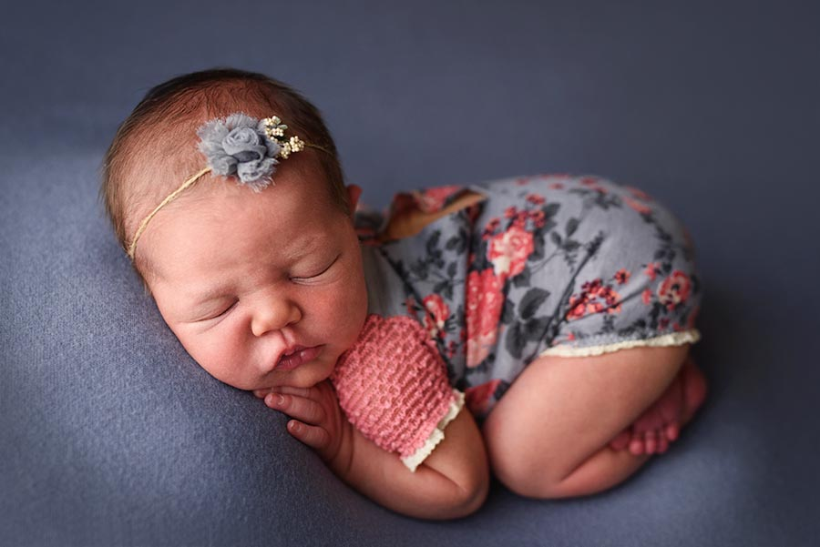 Newborn Photography of infant girl posed in tussle pose on blue gray wearing a romper from Adorable Props