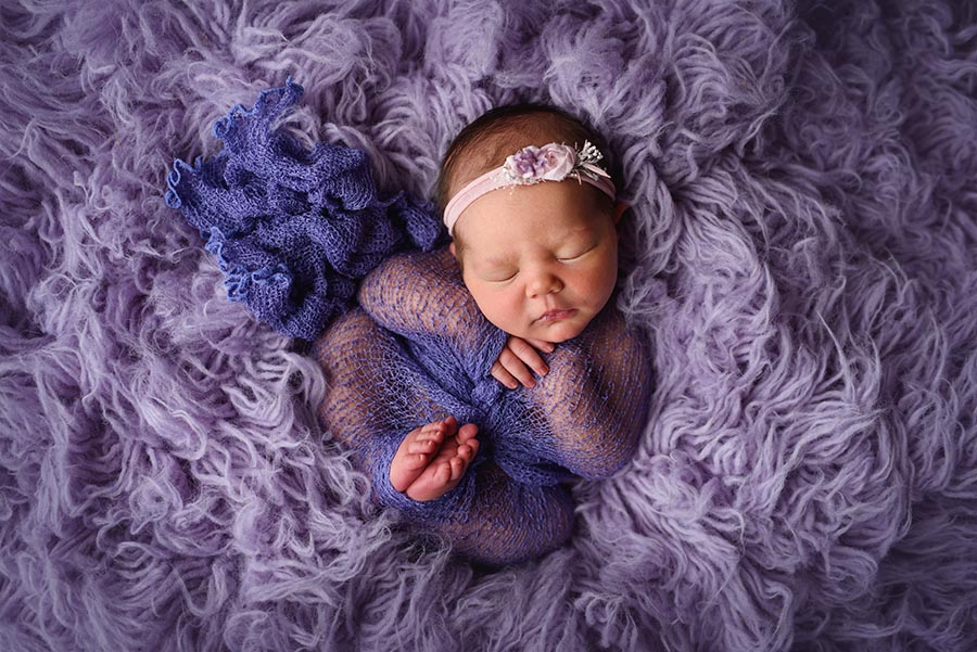 My favorite newborn pose, baby girl sweetly wrapped in purple on a purple flokati